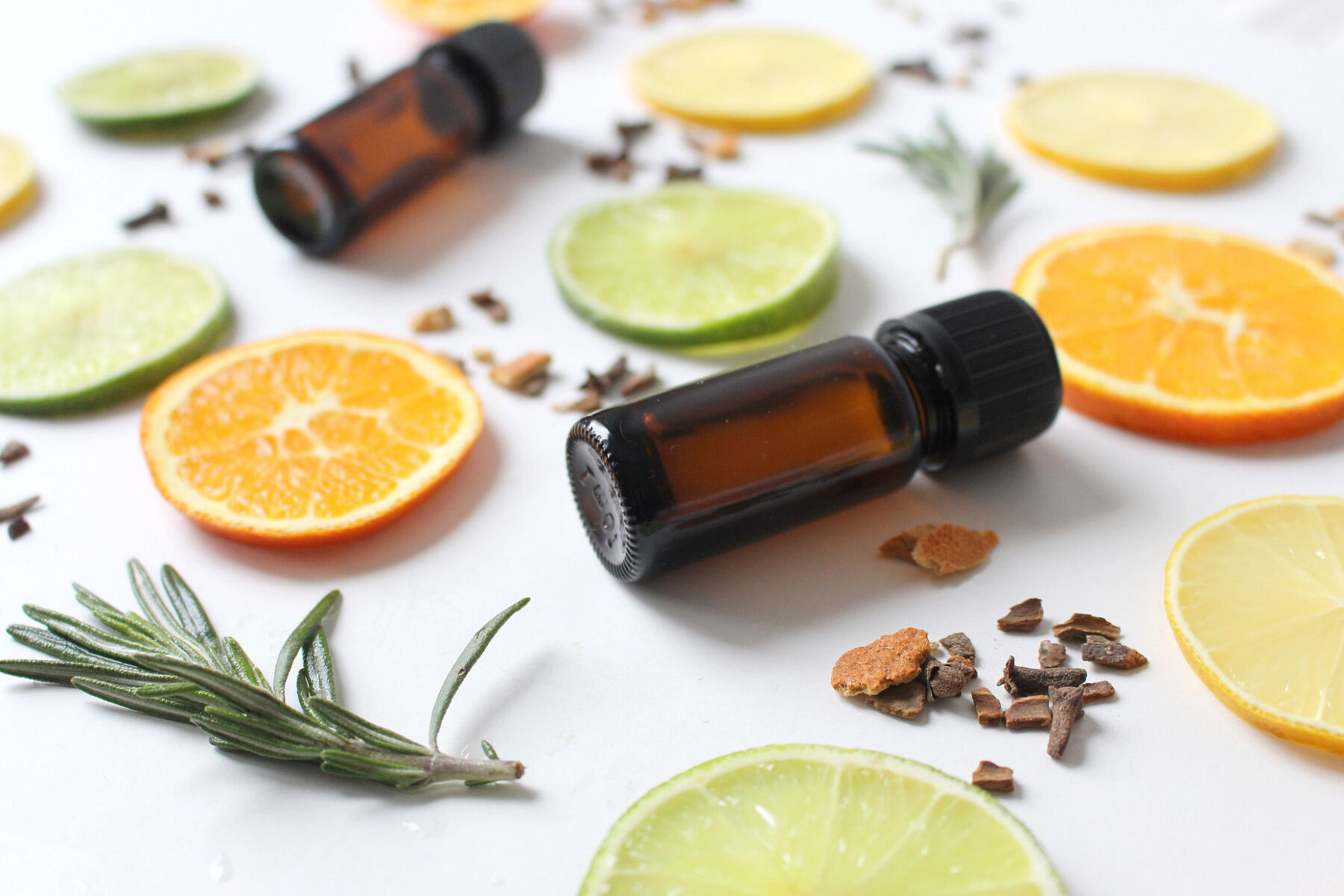 Two amber glass essential oil bottles surrounded by citrus slices and fresh rosemary