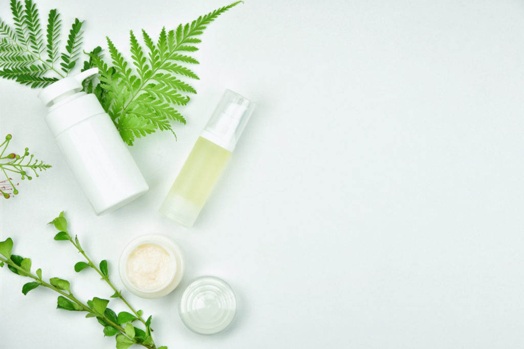 An assortment of natural bottles and jars on a white background with some green leaves