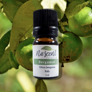 A 5ml bottle of bergamot essential oil in front of a photo of a bergamot tree