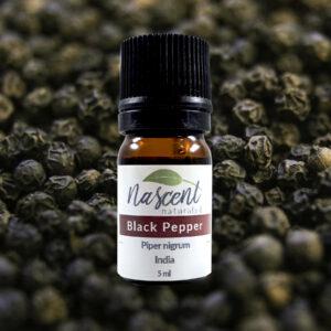5ml bottle of black pepper essential oil in front of a background of black pepper fruit