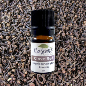 A 5ml bottle of Clove Bud essential oil in front of a background covered in clove buds