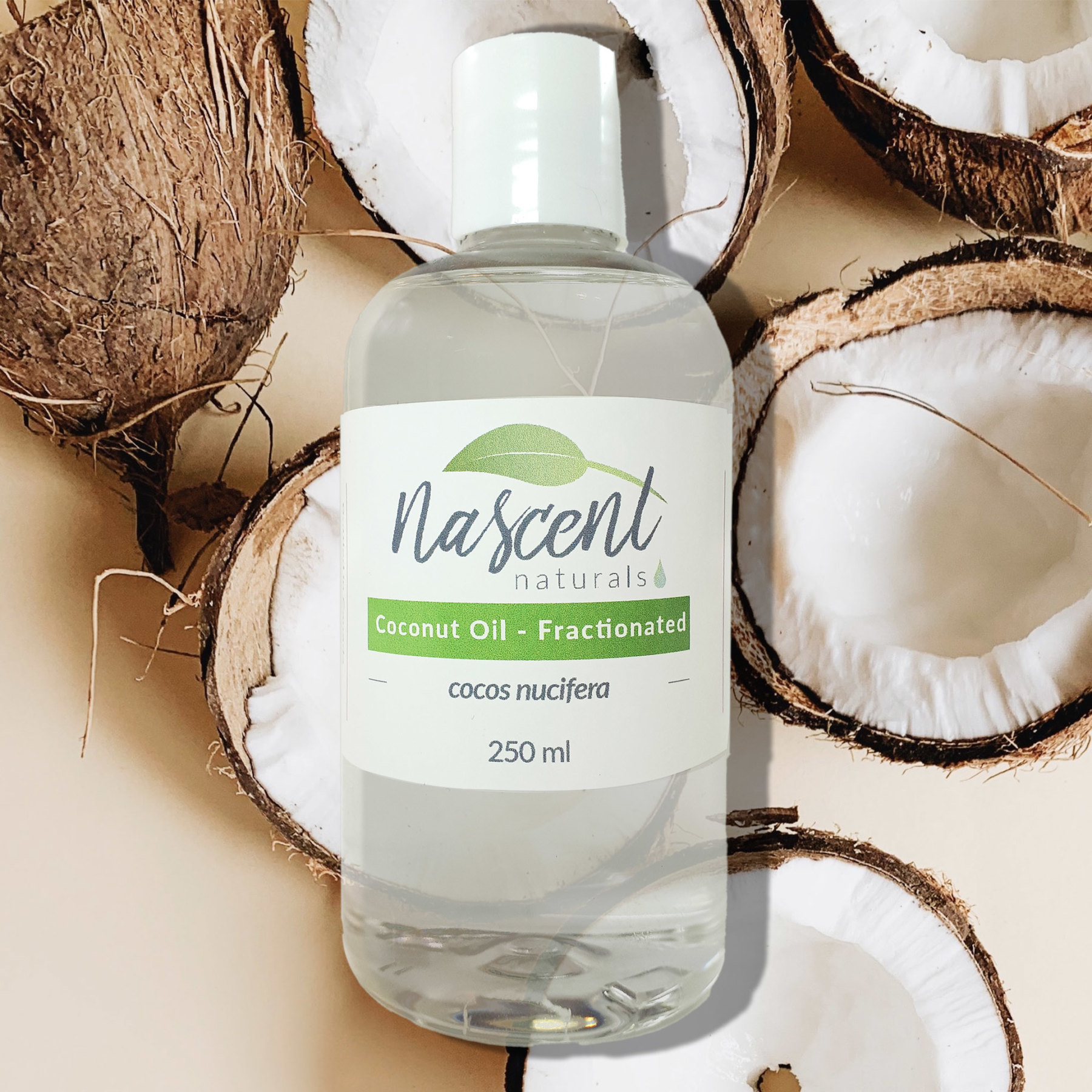 A two-hundred-fifty milliliter bottle of fractionated coconut oil in front of a photo background of cracked open coconuts