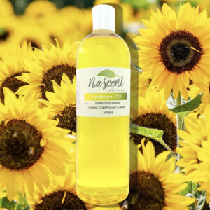 A five-hundred milliliter bottle of Sunflower oil in front of a photo background of sunflowers.