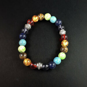 Chakra bead bracelet in front of a black background