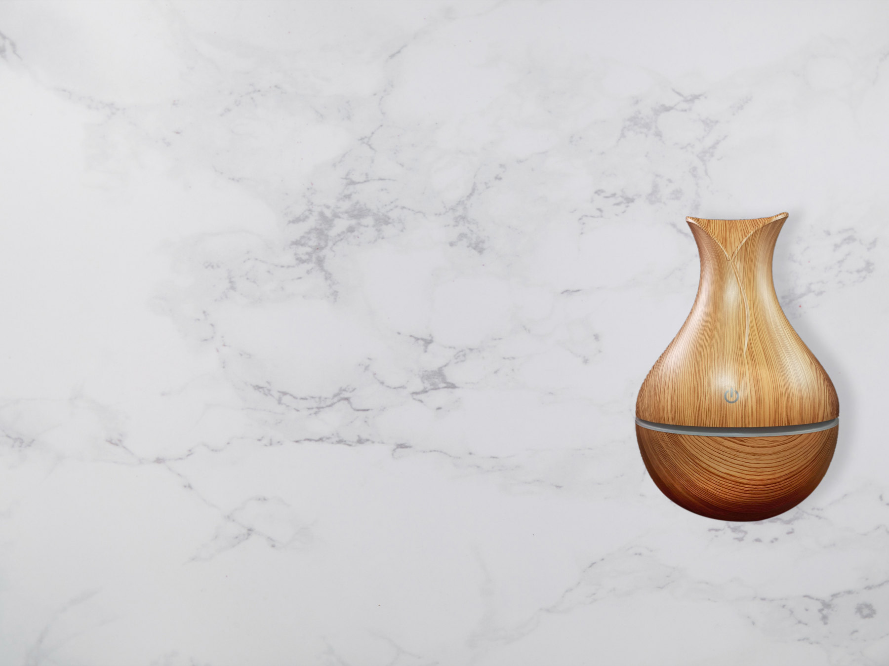 A light wood grain aromatherapy diffuser in front of a white marble background