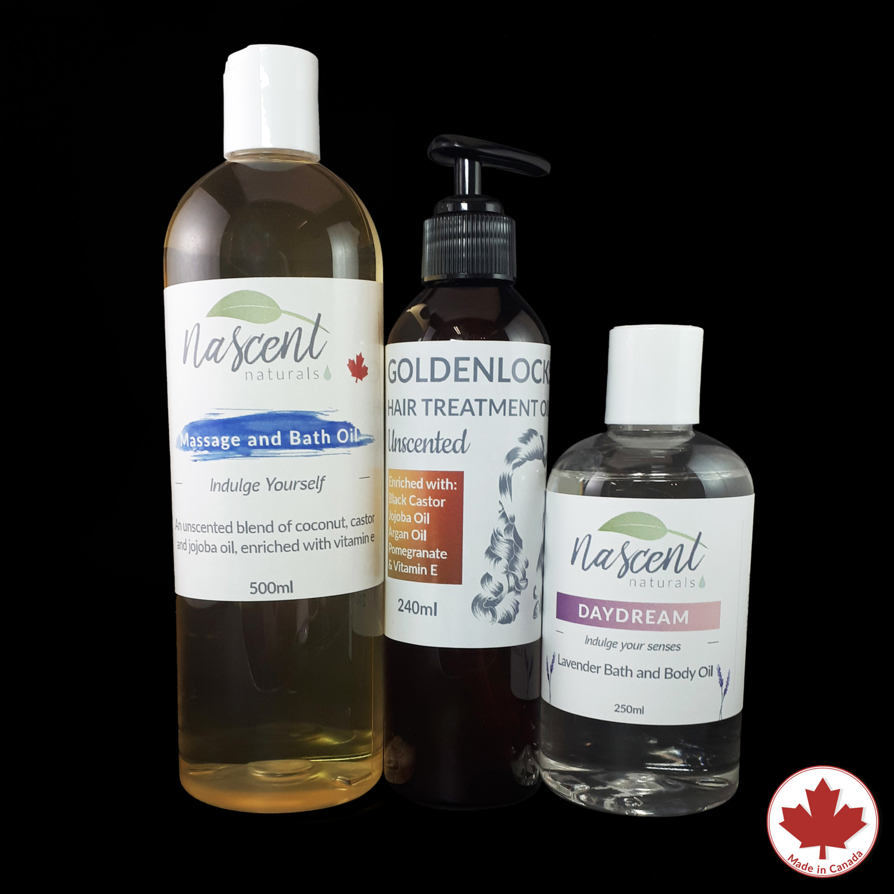 A bottle of massage oil base, a bottle of hair oil and a bottle of lavender bath oil in front of a black background