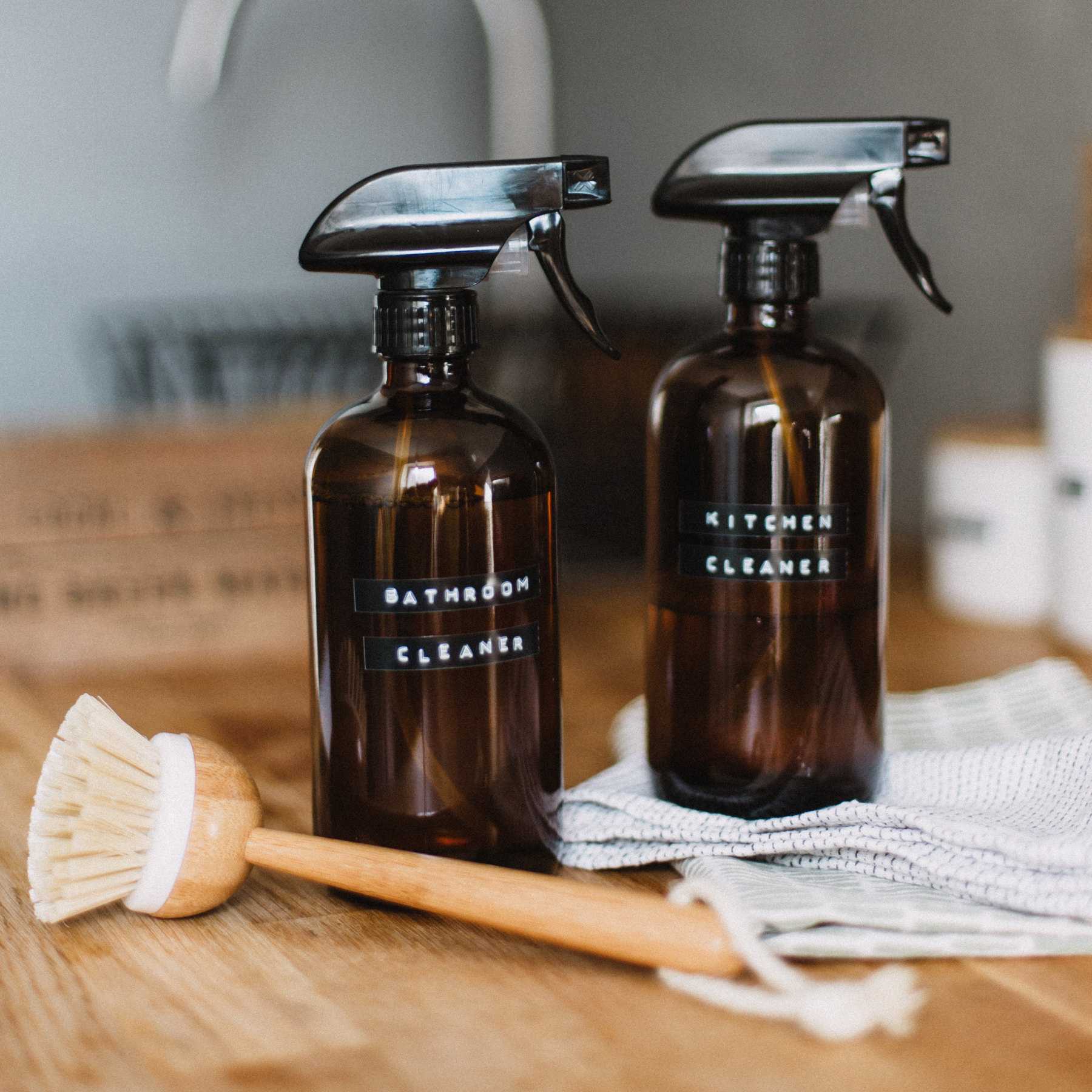 Two plastic amber bottles with black trigger spray caps. One bottle says 'bathroom cleaner' and the other says 'kitchen cleaners