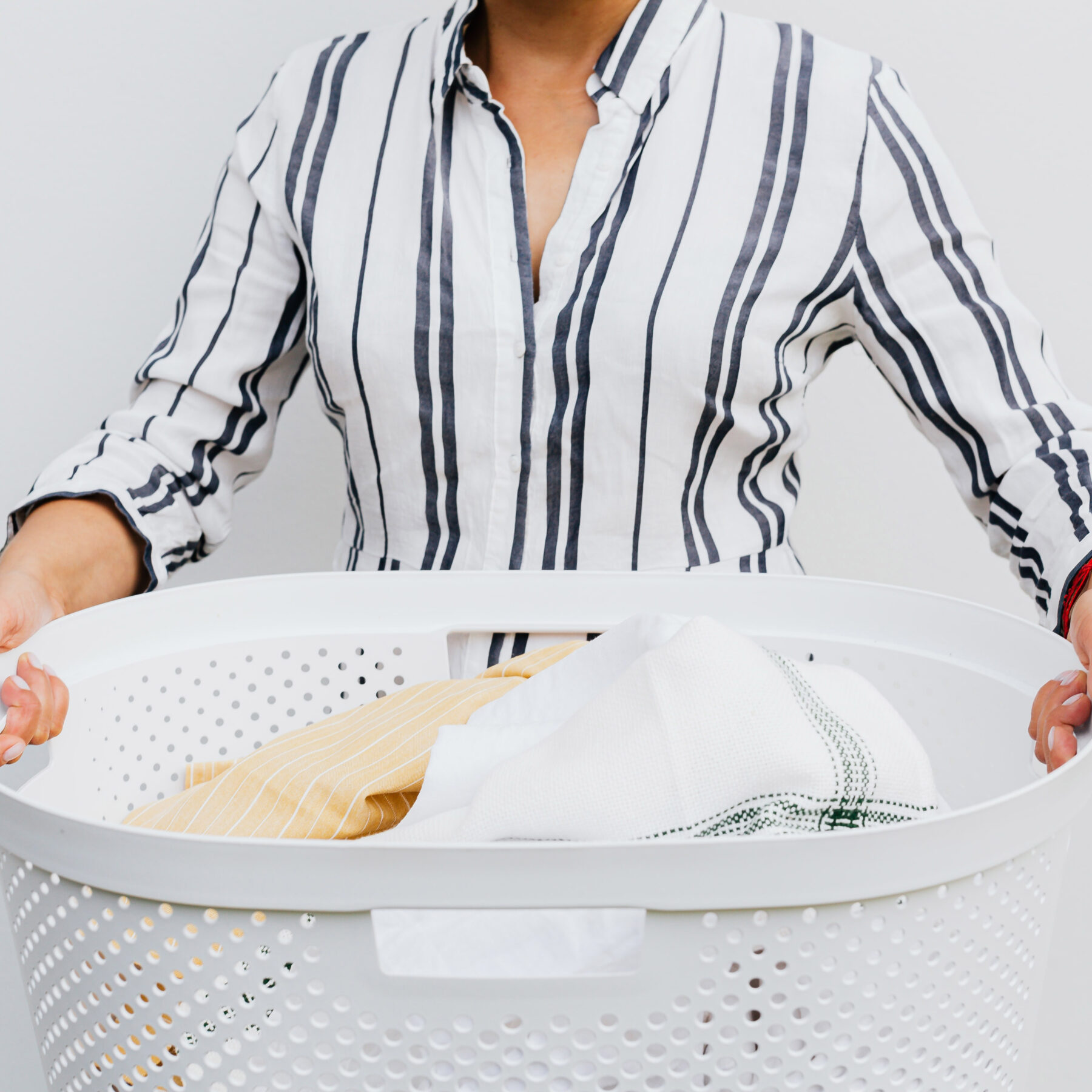 Someone in a white and blue striped shirt holding a white laundry basket